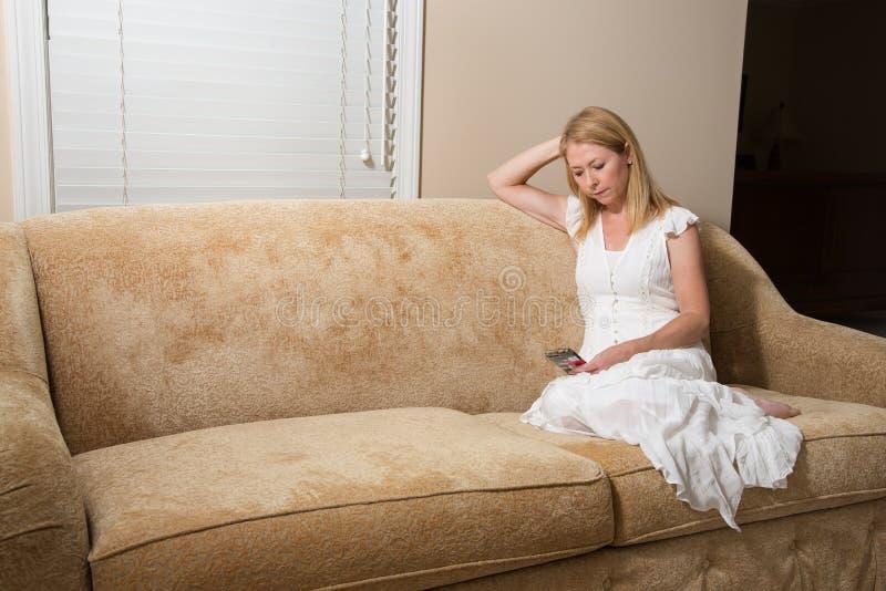 Vrouw het ontspannen op laag thuis met telefoon royalty-vrije stock fotografie