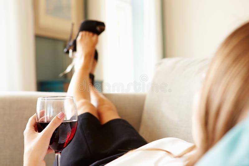 Vrouw het Ontspannen op Sofa With Glass Of Wine na het Werk stock foto's