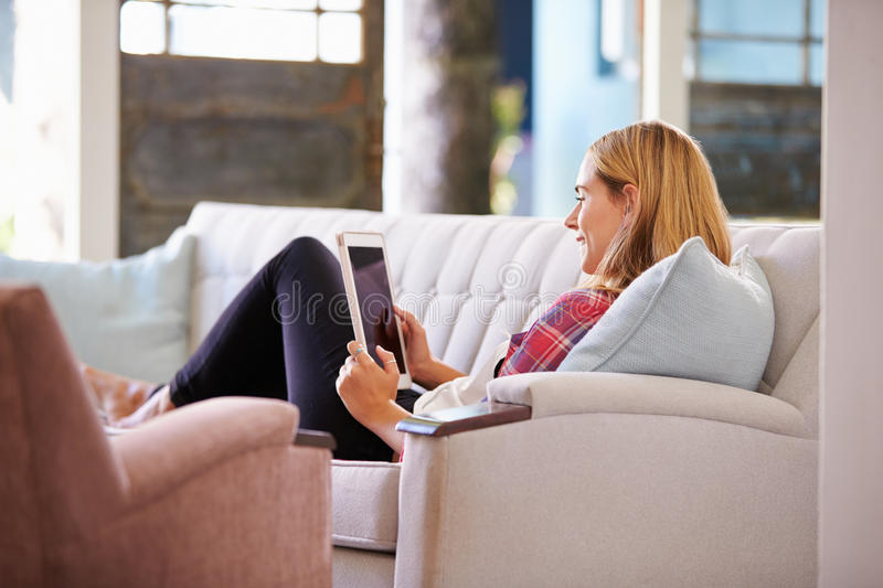Vrouw het Ontspannen op Sofa At Home Using Digital-Tablet stock foto