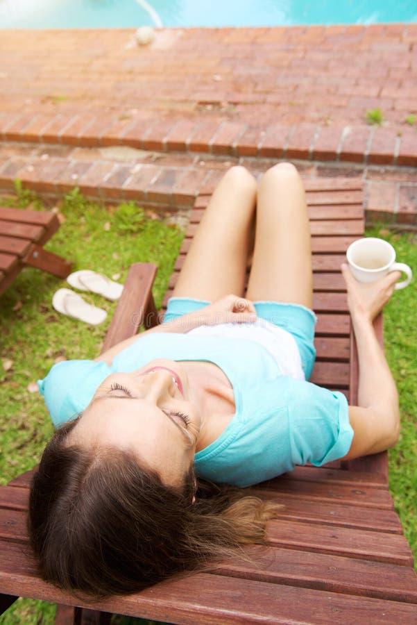 Vrouw het ontspannen op stoel door pool royalty-vrije stock foto's