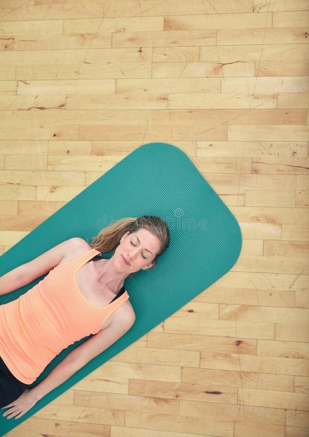 Vrouw het ontspannen op yogamat royalty-vrije stock fotografie