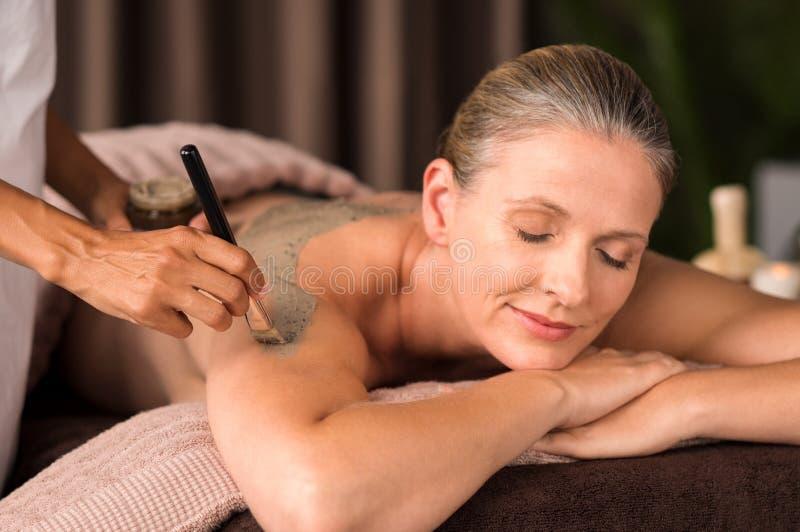 Vrouw het ontspannen tijdens modderbehandeling stock afbeeldingen