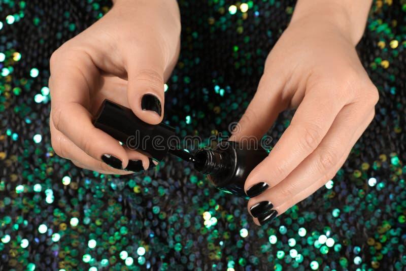 Vrouw het openen nagellakfles over stof met glanzende lovertjes stock afbeelding
