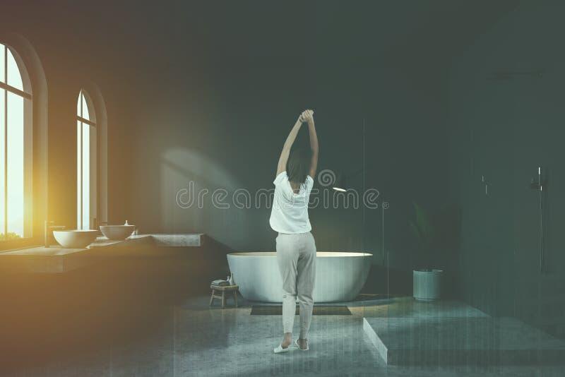 Vrouw in het overspannen binnenland van de vensters grijze badkamers royalty-vrije stock fotografie