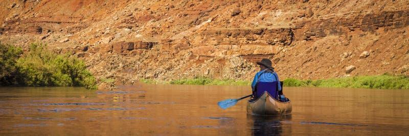 Vrouw het paddelen kano op woestijnrivier royalty-vrije stock foto's