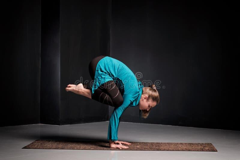 Vrouw het praktizeren de yoga, die Kraanoefening, Bakasana doen stelt, het uitwerken stock afbeelding