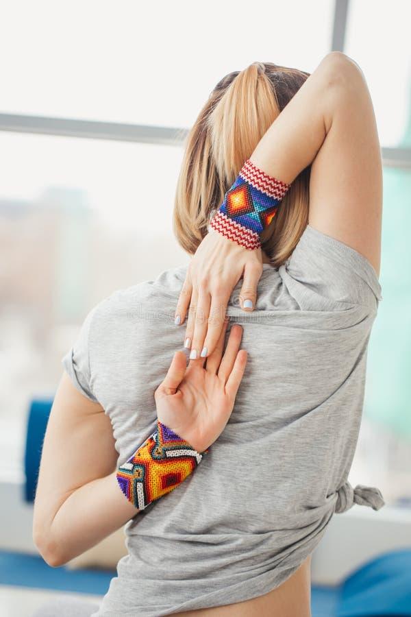 Vrouw het praktizeren de yoga, die in de oefening van het Koegezicht, Gomukasana zitten stelt, binnen binnenlandse achtergrond stock fotografie