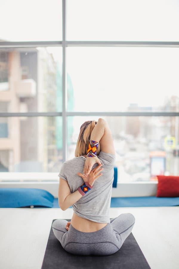 Vrouw het praktizeren de yoga, die in de oefening van het Koegezicht, Gomukasana zitten stelt, binnen binnenlandse achtergrond royalty-vrije stock foto