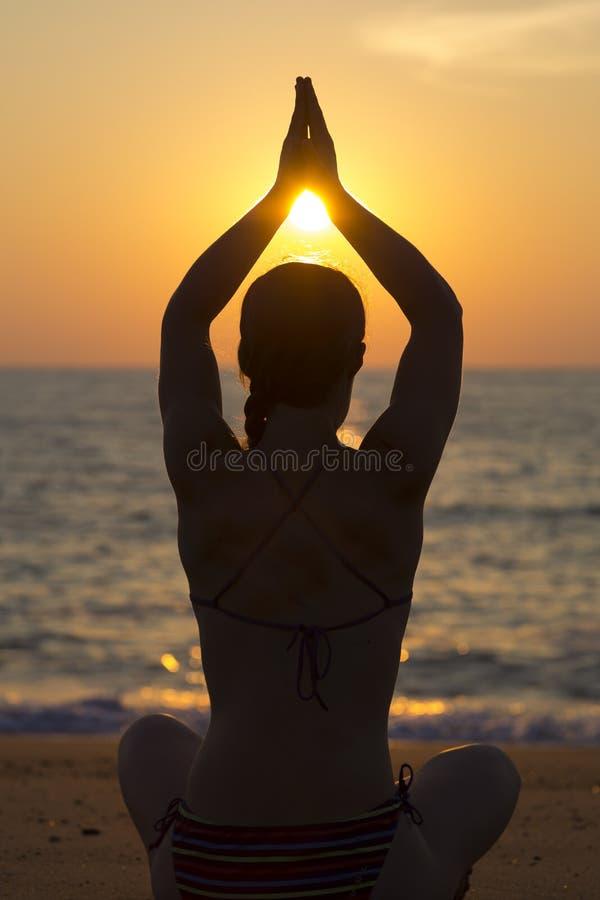 Vrouw het praktizeren yoga bij zonsondergang op het strand royalty-vrije stock fotografie