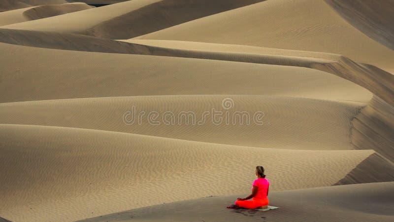Vrouw het praktizeren yoga in de zandduinen stock foto's
