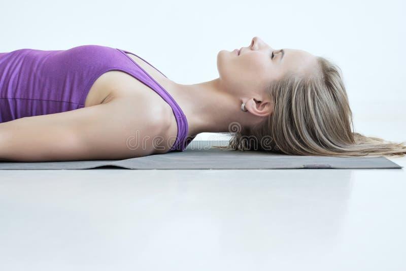 Vrouw het praktizeren yoga, die in Savasana-oefening liggen, die na yoga rusten stock afbeelding