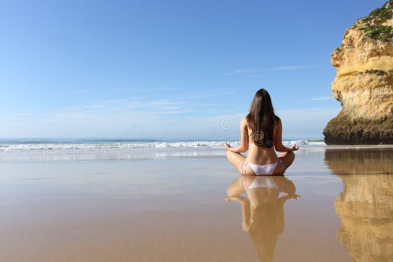 Vrouw het praktizeren yogaoefeningen op een solitair strand stock afbeeldingen