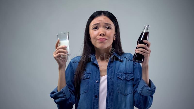 Vrouw het proberen aan koos tussen ongezonde sprankelende drank en nuttige gezonde melk stock foto's