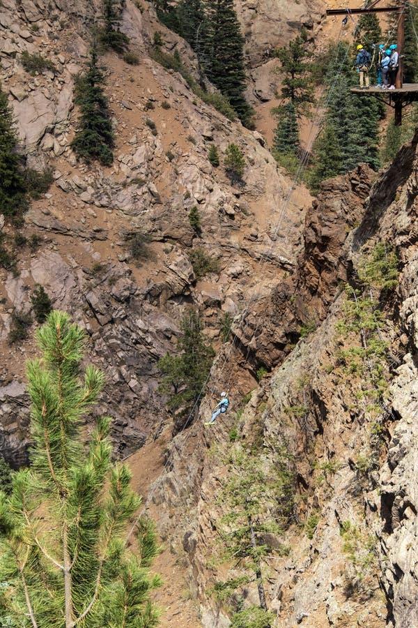 Vrouw het rappelling onderaan een steile en lange bergklip in de Rotsachtige Bergen met een groep die mensen op een platform op h stock foto