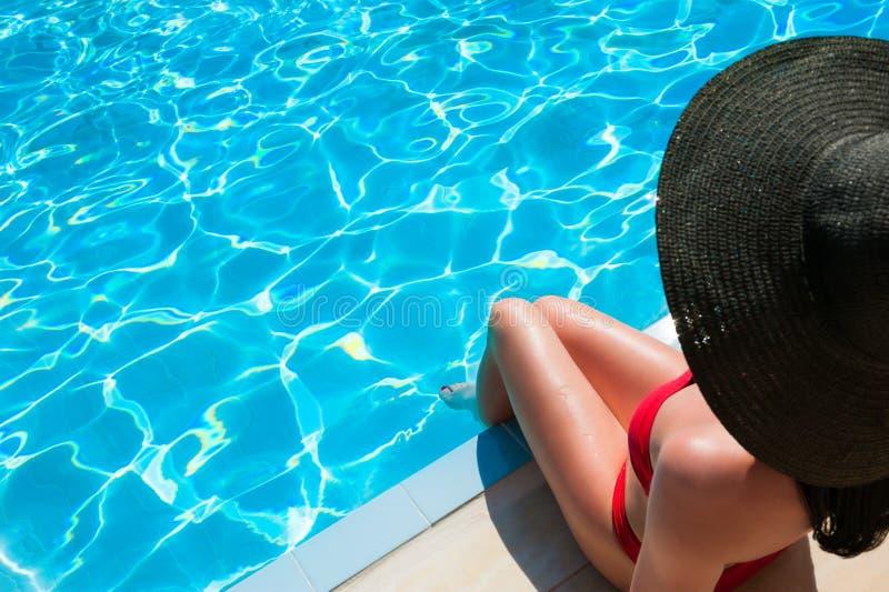 Vrouw in het rode bikini ontspannen in zwembad stock fotografie