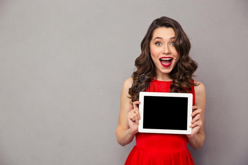 Vrouw in het rode de computerscherm van de kledings showig lege tablet stock afbeelding