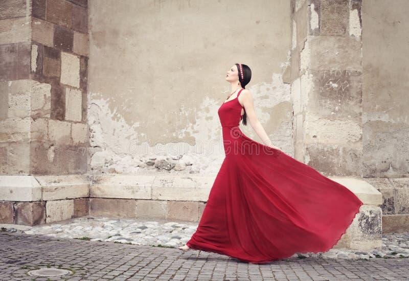Vrouw in het rode kleding lopen royalty-vrije stock foto