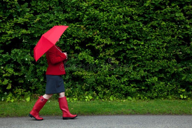 Vrouw in het rode lopen met paraplu royalty-vrije stock afbeeldingen