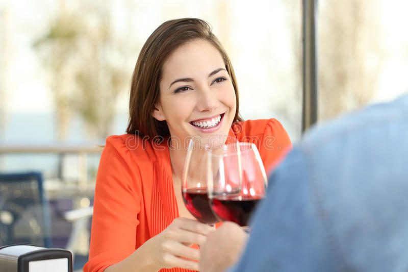 Vrouw het roosteren met wijn in een datum royalty-vrije stock afbeelding