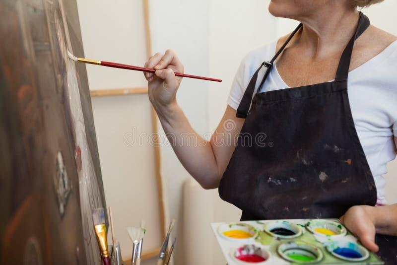 Vrouw het schilderen op canvas in tekeningsklasse stock foto