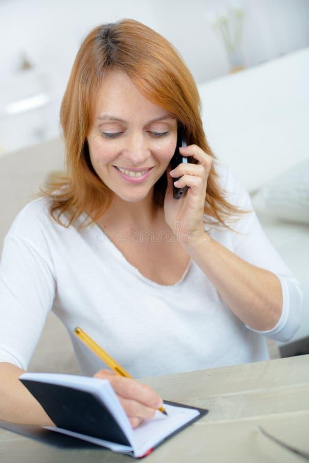 Vrouw het schrijven contactlijst van mobiele telefoon in agenda royalty-vrije stock foto