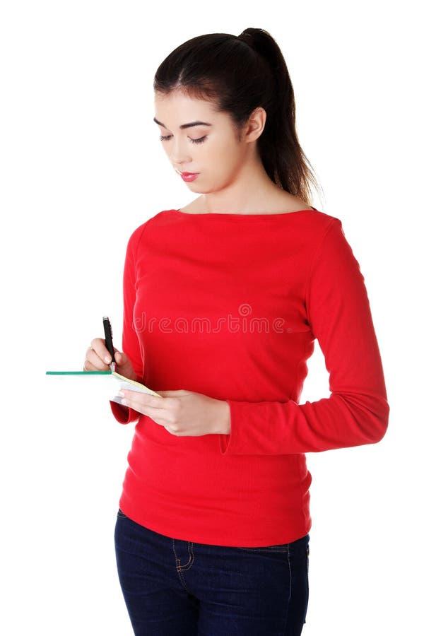 Vrouw het schrijven nota's en de planning van haar programma royalty-vrije stock afbeeldingen