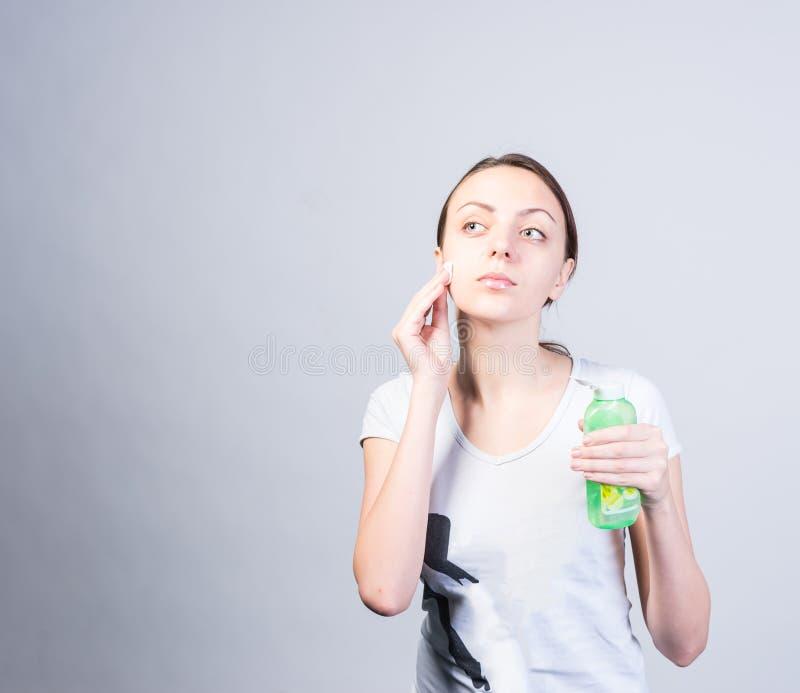 Vrouw het Schrobben Gezicht die Katoen met Reinigingsmiddel gebruiken royalty-vrije stock foto