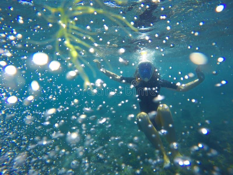 Vrouw het snorkelen in bellen, snorkelt in blauwe overzees royalty-vrije stock foto's