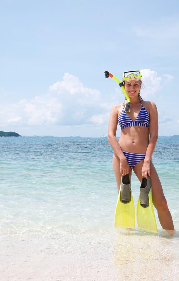 Vrouw het snorkelen het andsmiling in de vinnen van de waterholding royalty-vrije stock afbeeldingen