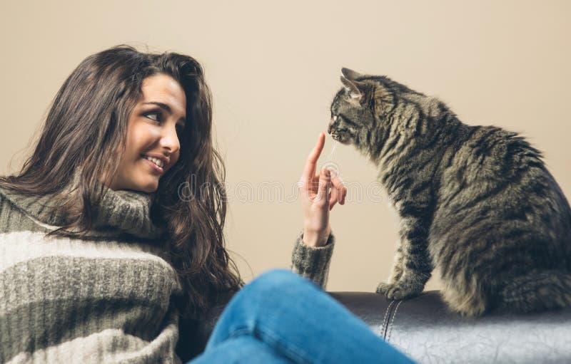 Vrouw het spelen met een kat stock afbeelding