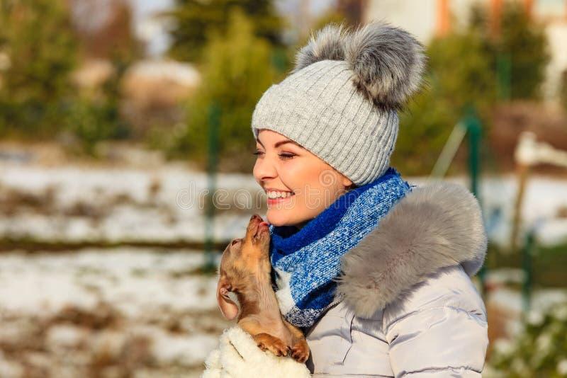 Vrouw het spelen met hond tijdens de winter royalty-vrije stock afbeeldingen