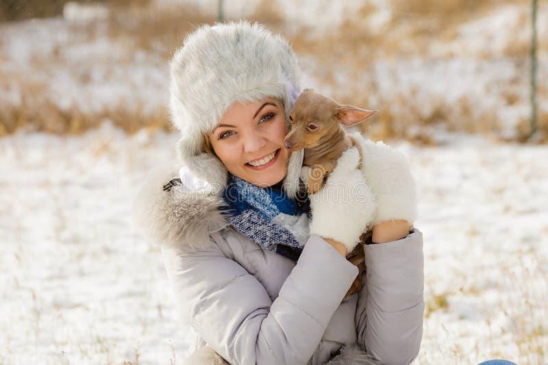 Vrouw het spelen met hond tijdens de winter royalty-vrije stock afbeelding