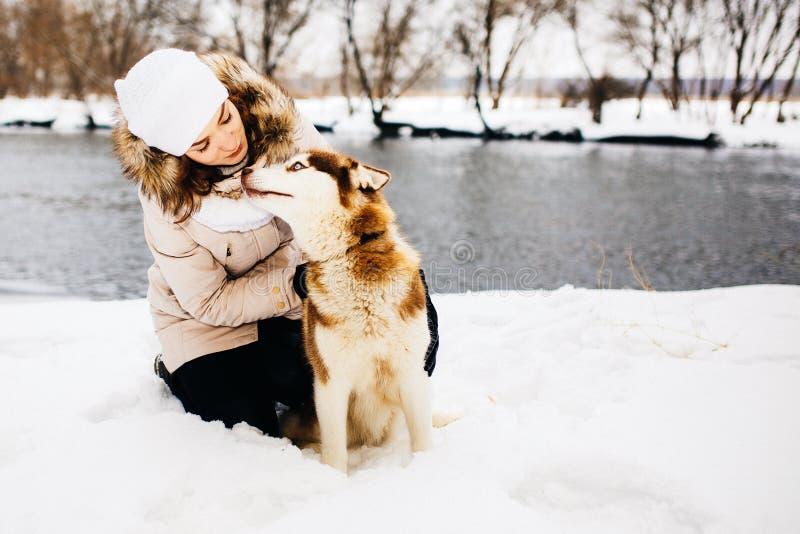 Vrouw het spelen met rode Siberische schor hond in sneeuwpark gestemd royalty-vrije stock afbeeldingen