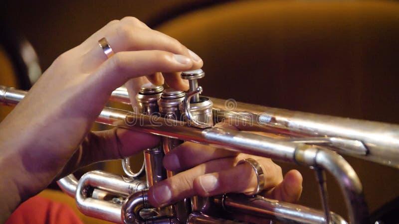 Vrouw het spelen trompet Nadruk op de vinger van de saxofoonspeler Trompetter het spelen het instrument van de muziekjazz Het ins stock foto's