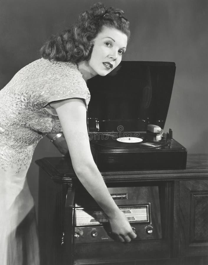 Vrouw het spelen verslagalbum op fonograaf stock foto's