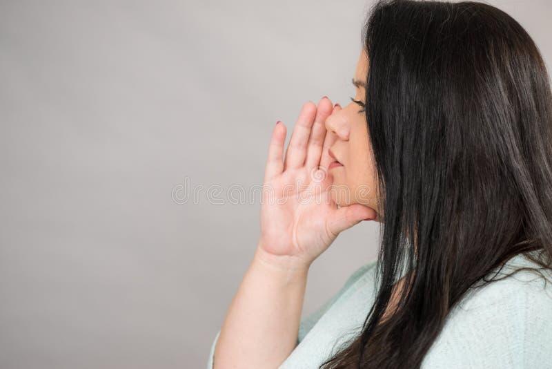 Vrouw het spreken geruchten of het fluisteren royalty-vrije stock afbeelding