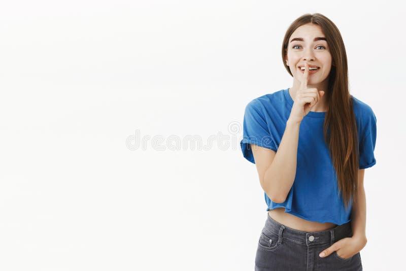 Vrouw het spreken met vriend het grinniken het zeggen shh bij camera het vragen houdt stil zodat luistert niemand grappig gerucht stock foto