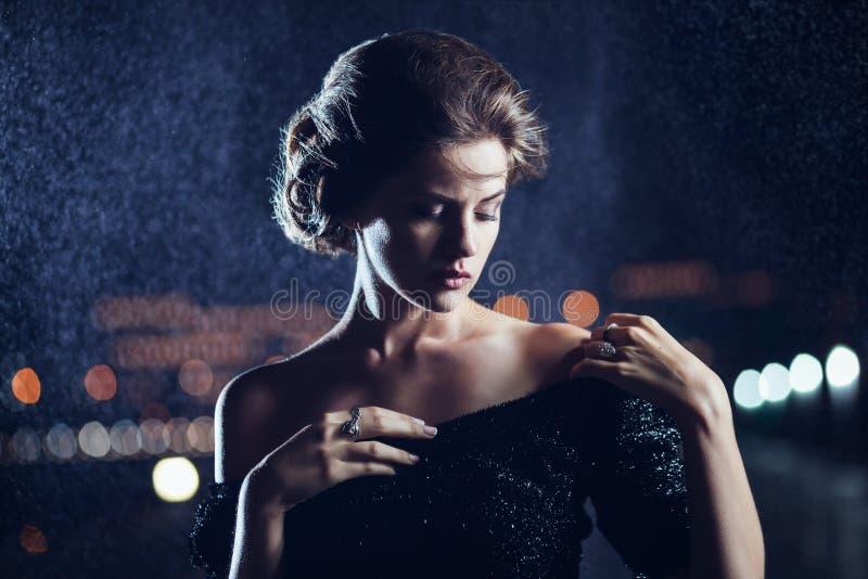 Vrouw het stellen in de regen royalty-vrije stock afbeelding