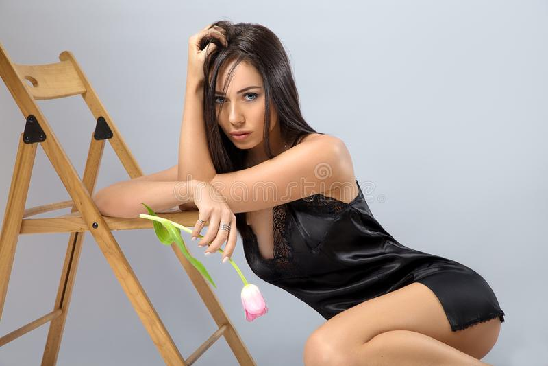 Vrouw het stellen in de zwarte lingerie met bloem royalty-vrije stock fotografie