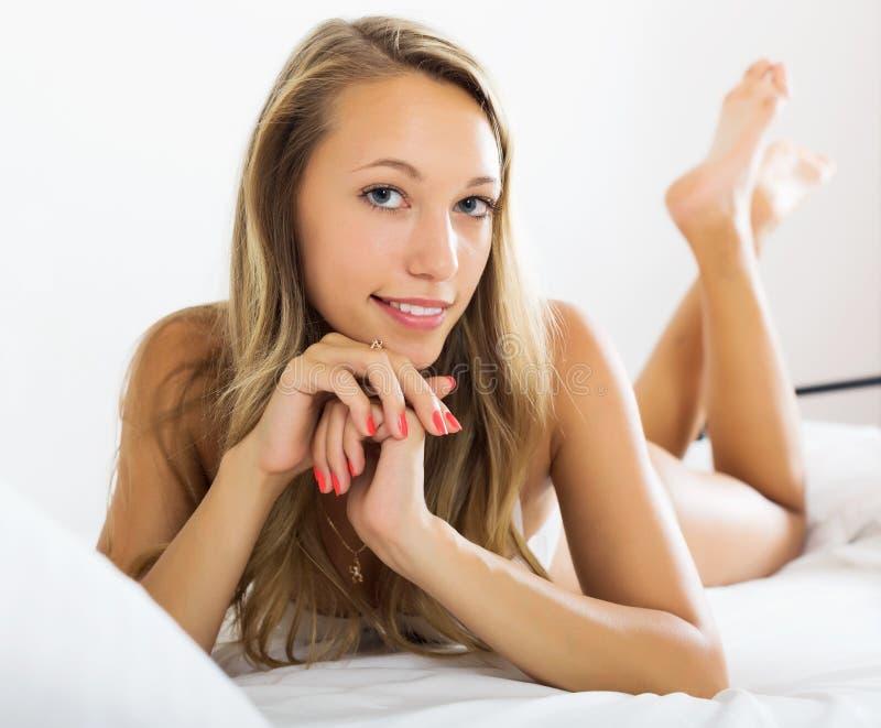Vrouw het stellen op bed royalty-vrije stock afbeelding