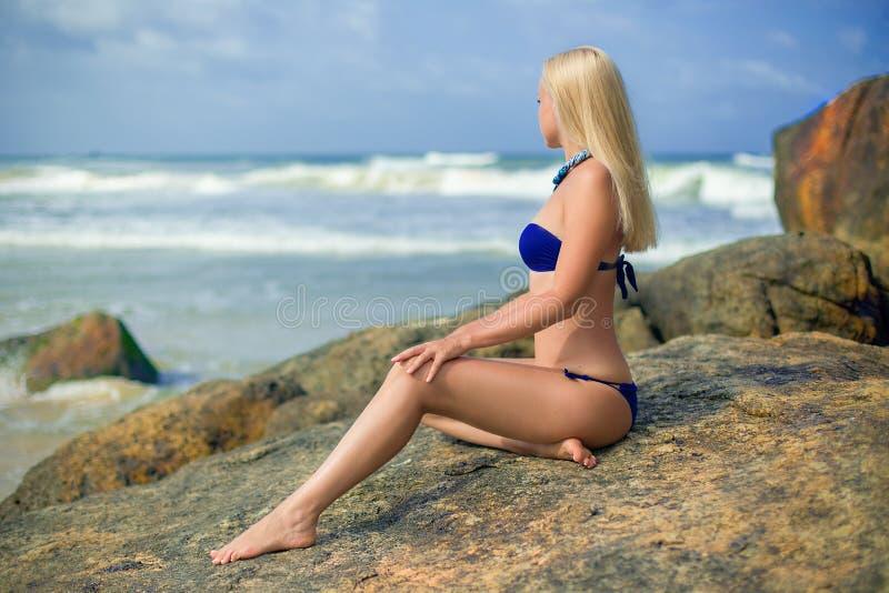 Vrouw het stellen op de rots in de oceaan stock foto's