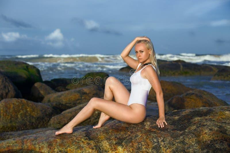 Vrouw het stellen op de rotsen in de oceaan stock fotografie