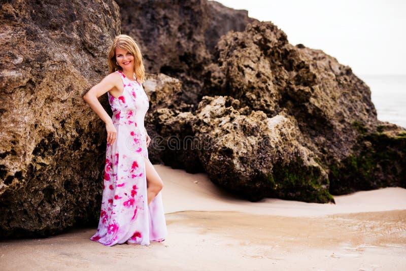 Vrouw het stellen op de strandrotsen royalty-vrije stock fotografie