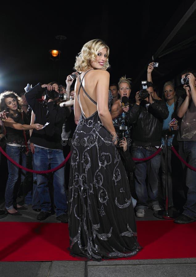 Vrouw het Stellen op Rood Tapijt in Front Of Fans royalty-vrije stock afbeelding