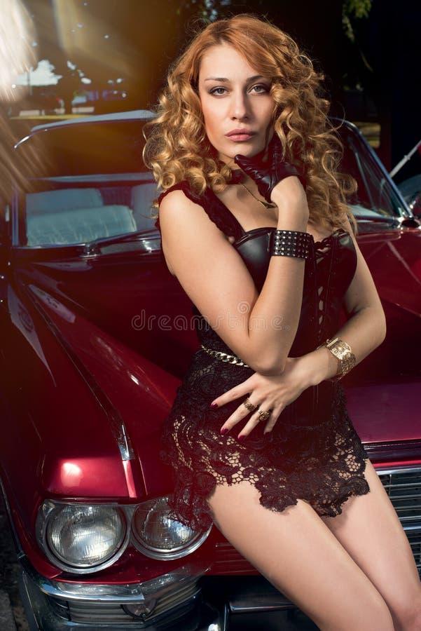 Vrouw het stellen over retro auto stock afbeeldingen