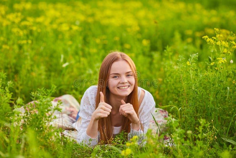 Vrouw het stiiting op het groene gras royalty-vrije stock foto