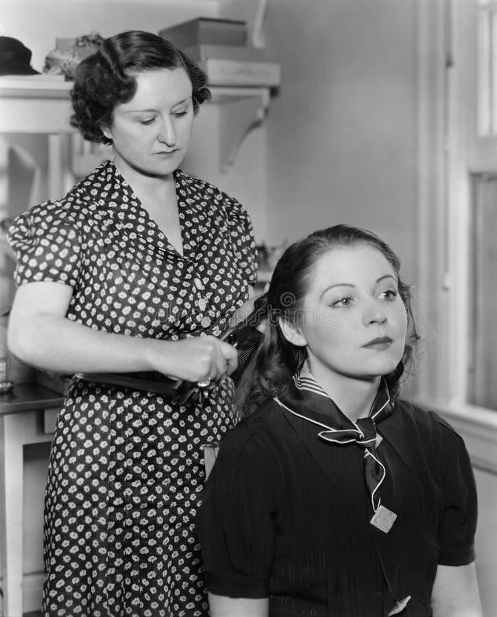 Vrouw het stileren het haar van een andere vrouw royalty-vrije stock foto's