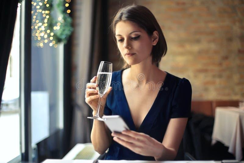 Vrouw het texting in een restaurant stock afbeeldingen