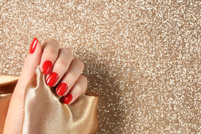 Vrouw het tonen manicured hand met rood nagellak op kleurenachtergrond, hoogste mening royalty-vrije stock foto