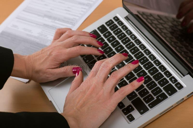 Vrouw het typen op laptop in het bureau, handenclose-up stock foto's